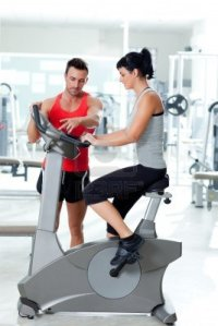 11982240-woman-on-stationary-bicycle-with-personal-trainer-at-fitness-gym