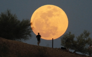 a-runner-makes-his-way-along-a-trail-on-a-butte-in-front-of-the-super-moon-at-papago-park-in-phoenix-arizona-may-5-2012-a-super-moon-will-light-up-saturdays-night-sky-in-a-once-a-year-cosmic-s
